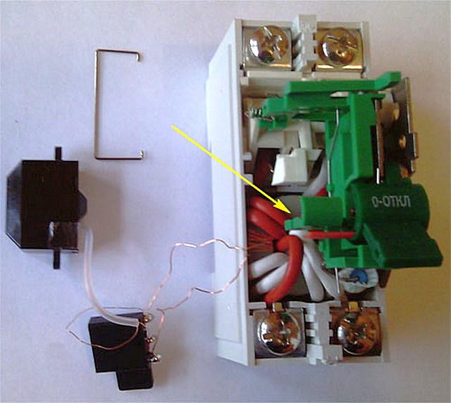 На иллюстрации стрелкой показан дифференциальный трансформатор с тороидальным сердечником и тремя обмотками.