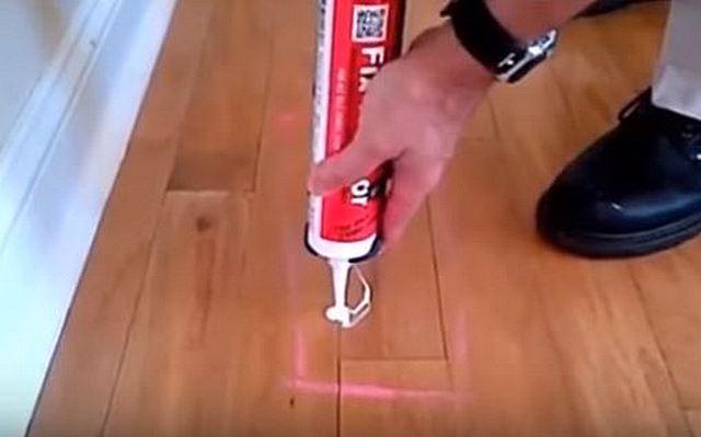 С помощью шприца-пистолета и отверстия и вязель между досками на намеченном участке плотно заполняется ремонтным клеем