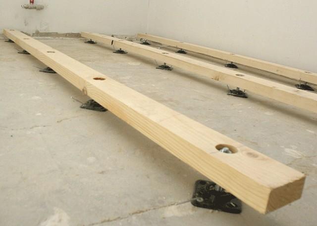 Установка лагов на специальные подставки, дающие возможность точной регулировки высоты бруса.