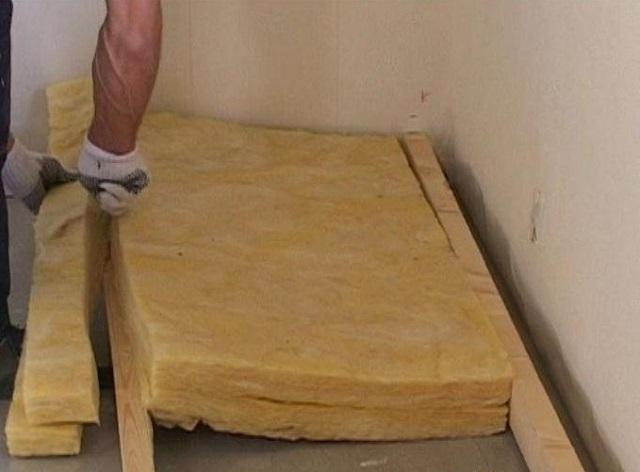 Укладка минеральной ваты между лагами. А чтобы не подрезать вот так края блоков, следует лаги сразу устанавливать с шагом, обеспечивающим их плотную укладку.