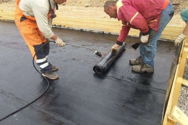 Выполнение гидроизоляции из рулонных материалов на основе битума по бетонной подготовке.
