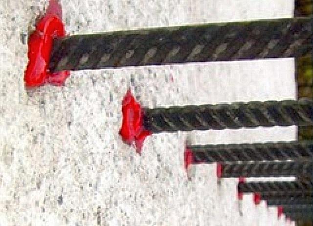 Арматурные пруты, закреплённые химическими анкерами в пористом материале несущей стены.