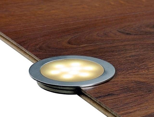 Современные светильники для подсветки пола могут быть столь тонкими, что помещаться даже в обычном напольном жестком покрытии – ламинате, доске, керамической плитке и т.п.
