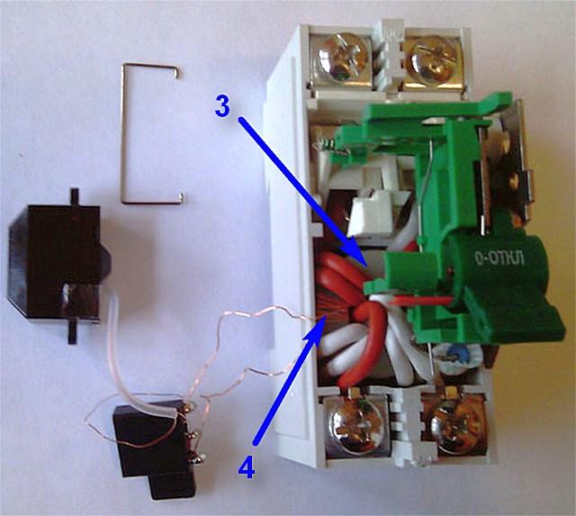 Устройство УЗО – главным элементом является дифференциальный трансформатор. Хорошо видны его обмотки фазой и нулем – толстые провода белого и красного цвета.