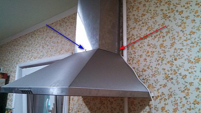 Двух штатных саморезов (красная стрелка), обеспечивающих крепление верхнего декоративного короба к корпусу вытяжки оказалось недостаточно. Дополнительный саморез (синяя стрелка), установленный с фронтальной части, устранил явление вибрационного шума.