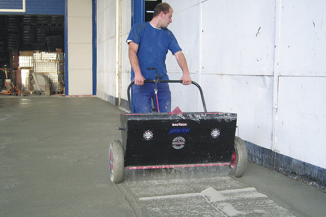 Использование специальных тележек-дозаторов позволяет добиться максимальной равномерности распределения топпинга по поверхности бетона.