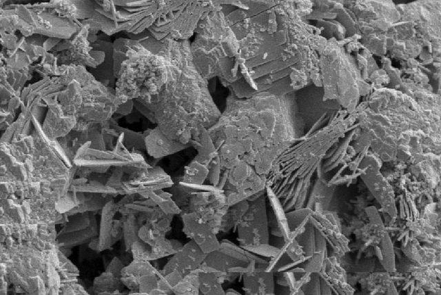 Под микроскопом бетон предстаёт весьма рыхлой неоднородной структурой с многочисленными пустотами.
