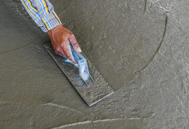 Железнение свежеуложенной бетонной стяжки сухим цементом – с некоторым упрощением это можно считать прообразом упрочнения с помощью топпинга.
