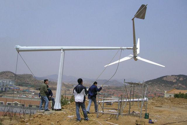 Установка мачты с ветрогенератором с шарнирным соединением нижней и верхней секции и общим их креплением к фундаменту.