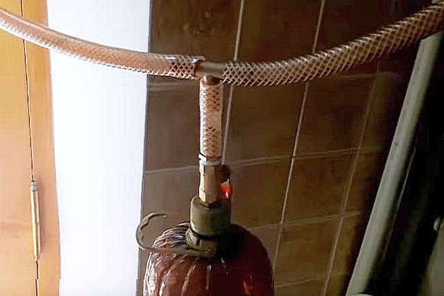 Простейший сборник конденсата, сделанный из пластиковой бутылки и одеваемый через тройник на трубу подачи дыма в коптильную камеру.