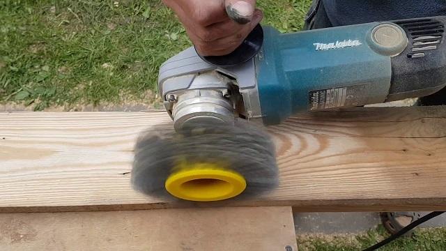 Обработка доски шлифмашинкой с металлической щеткой. Все хорошо, но вот только мастер работает голыми руками. Не берите с него пример – не пренебрегайте средствами защиты!