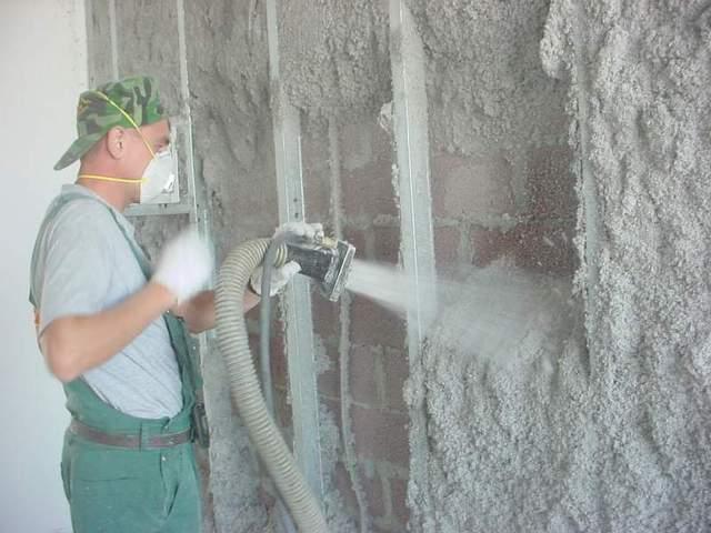 Утепление стены изнутри напылением эковаты. Хорошо видны направляющие каркаса, к которому затем будет крепиться обшивка.