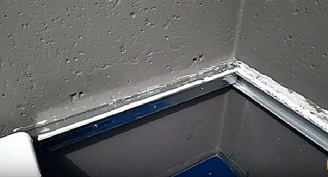 Нанесение герметика на закрепленный на стенах металлический профиль.