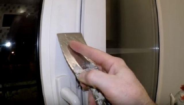 Удаление остатков пены с пластикового окна с помощью шпателя