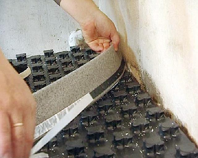 Установка демпферной ленты по периметру комнаты между термоизоляционными матами и стенами – для последующей заливки создаваемого «теплого пола» стяжкой.
