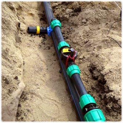Аккуратно укладываем трубы и прочие элементы системы в канаву