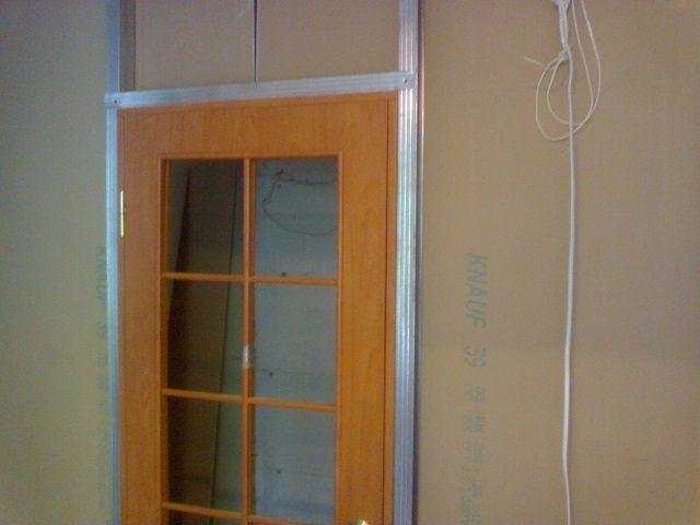 Перегородка из гипсокартона с установленной дверной коробкой и дверью
