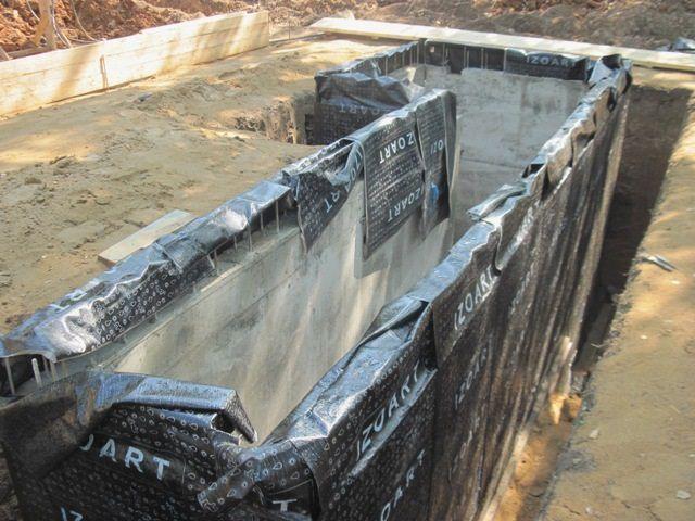 Пространство между гидроизолированными стенками ямы и котлована аккуратно и плотно заполняется глиняно-грунтовой смесью.