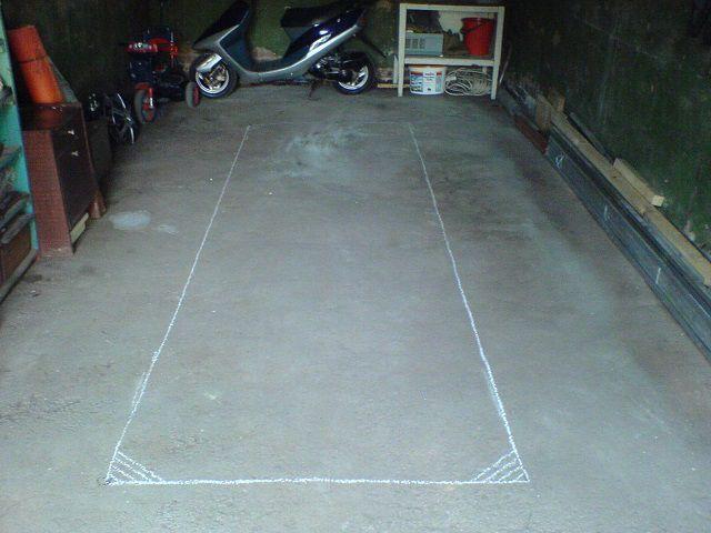 Разметка контура будущей ямы на бетонированном полу гаража