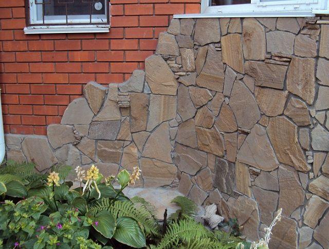 Участок внешней стены дома, отделанный натуральными каменными плитами