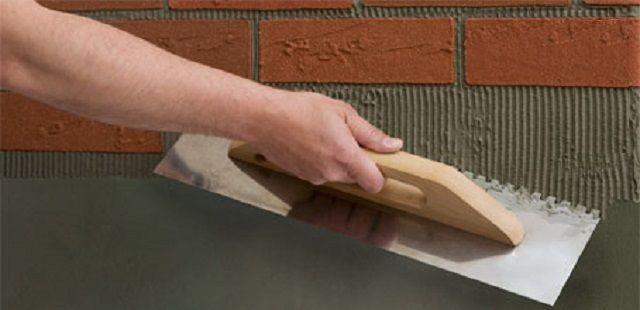 Распределение клея по поверхности отделываемой стены зубчатым шпателем