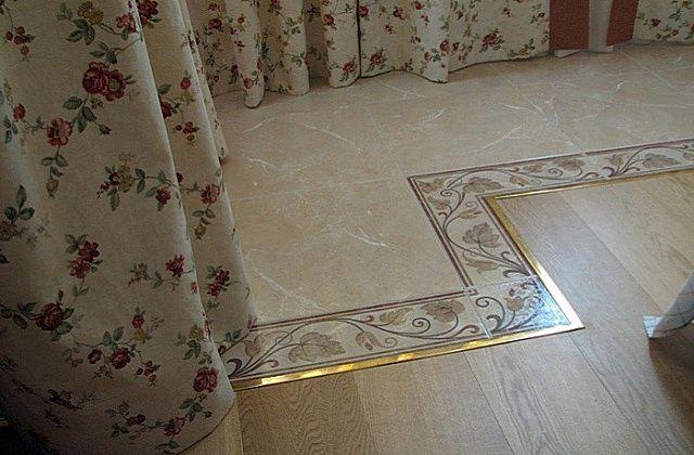 Металлический молдинг разделяет области керамической плитки и ламината на полу