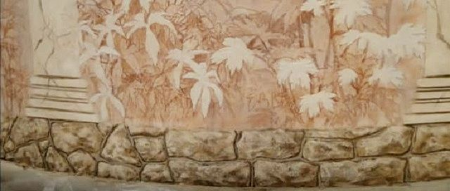 Вот такой каменный рельеф, пущенный по нижней части стены, можно выполнить собственными силами
