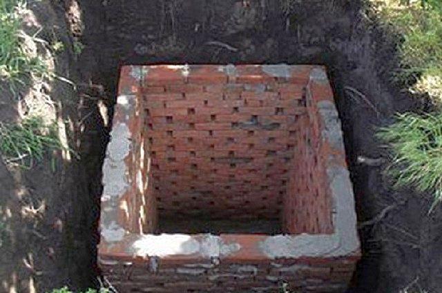 Дренажная яма со стенками, выложенными из красного кирпича
