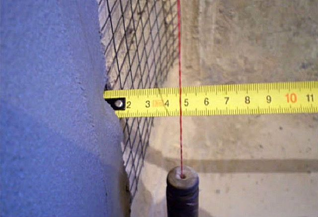 Нехитрое приспособление – обычный отвес, но позволяет провести ревизию неровностей стены с высочайшей точностью