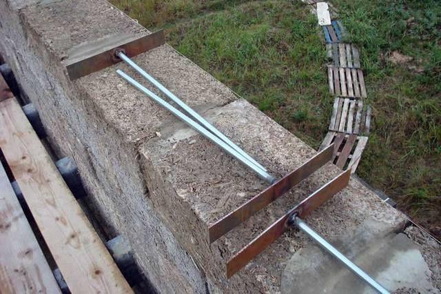 Пластины с приваренными шпильками – они будут установлены при кладке последнего ряжа блочной стены. (Блоки на картинке показаны арболитовые, но принципа это не меняет).