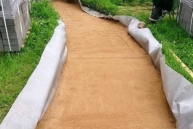 Геотекстиль большой плотности, помимо разделительных функций, сыграет и роль дренажа под укладываемой дорожкой