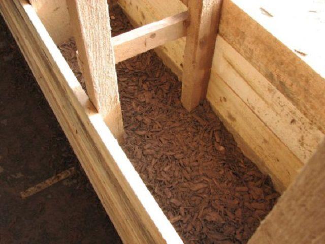 Обработанные опилки засыпаются в полость между внутренней и внешней обшивками каркасной стены
