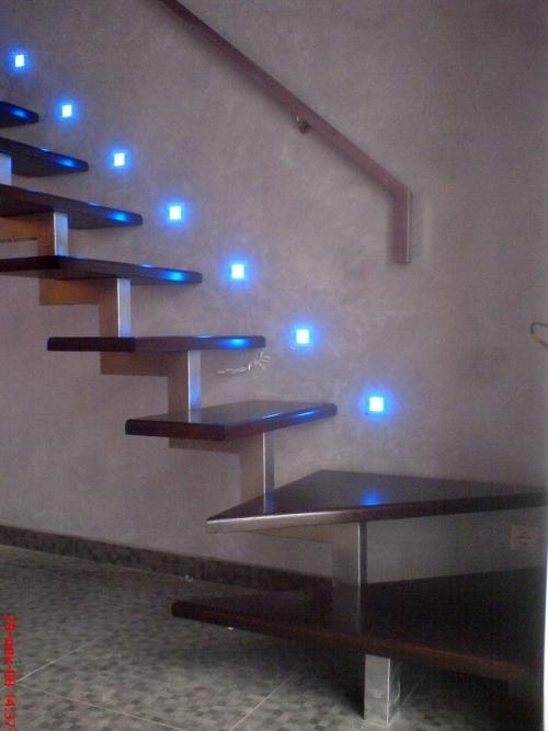 Точечные светильники так же, как и светодиодные ленты могут освещать лестницу разным цветом. Кстати, подниматься по такой лестнице, не имеющей внешнего ограждения, в потемках — весьма рискованное дело