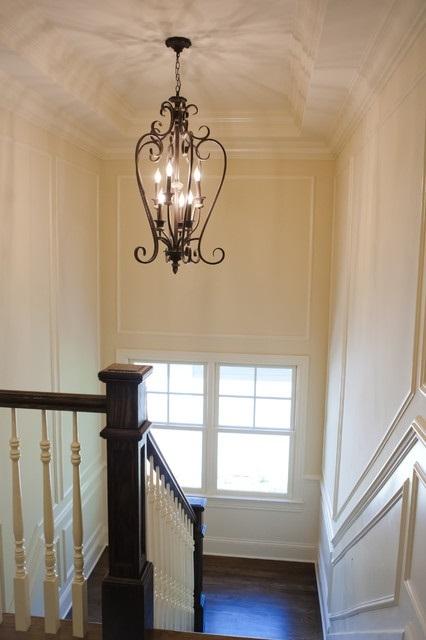 Если над лестничным маршем имеется высокий потолок, то освещение можно организовать и с помощью оригинальной люстры, гармонирующей со стилевой отделкой интерьера